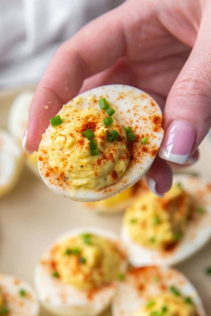 Hand holding deviled egg with no mustard and sprinkled with paprika and chives