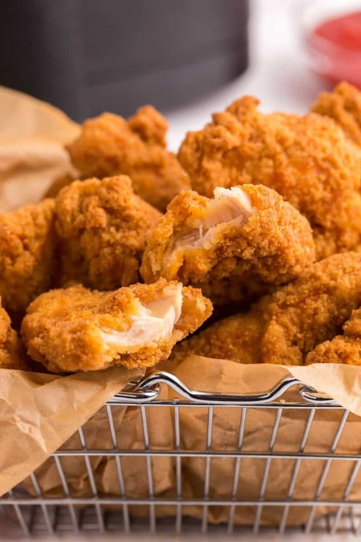 Closeup of chicken tenders in a wire basket with parchment paper