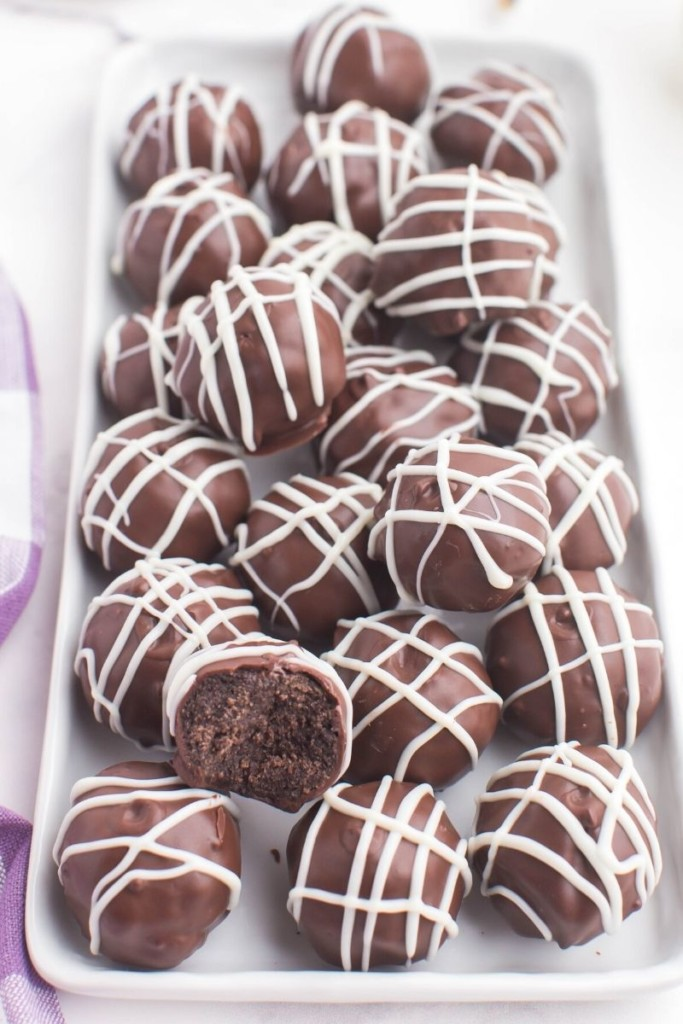 Oreo truffles without cream cheese plated on a rectangular serving plate with one that has been bitten into