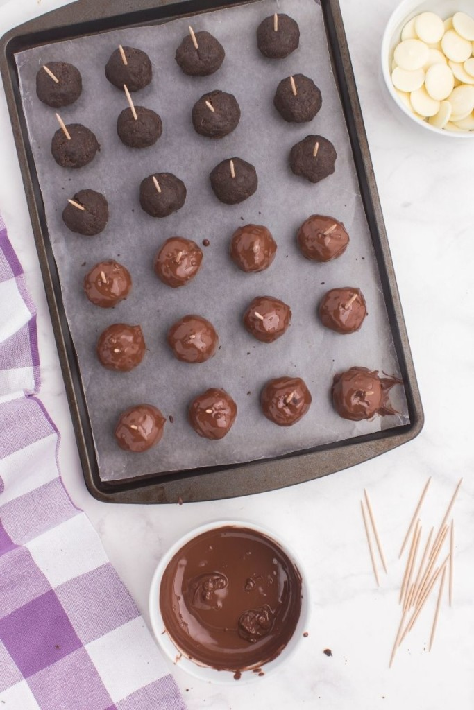 Oreo truffles with toothpicks in them and half of them covered in chocolate on a baking sheet and dipping sauce next to it