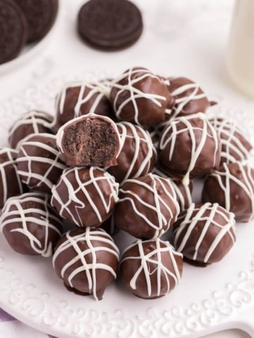 Oreo Balls on a white circular plate drizzled with white chocolate and one bitten into