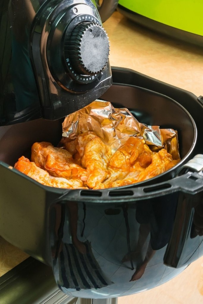 Basket being pulled out of the air fryer with sauced wings inside