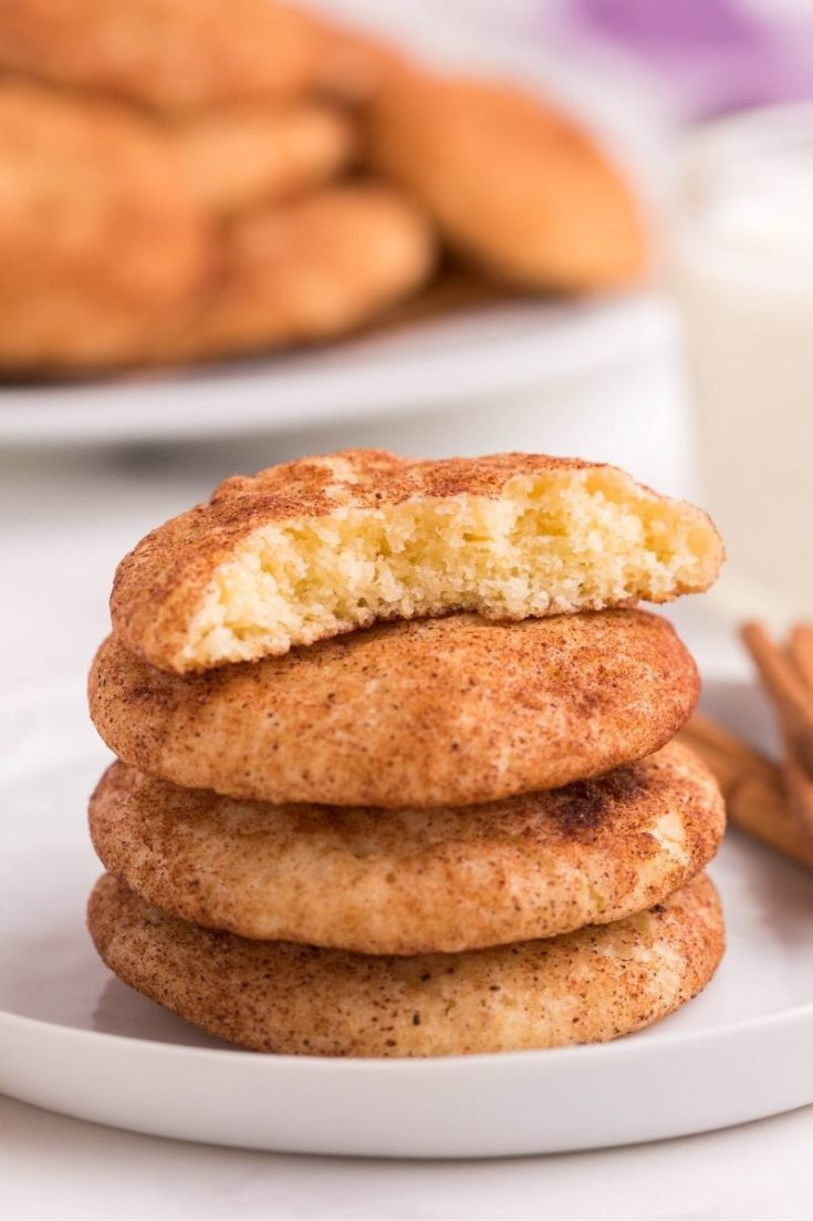 Snickerdoodle cookie with no cream of tartar stacked on top of each other on a white plate with top cookie broken in half