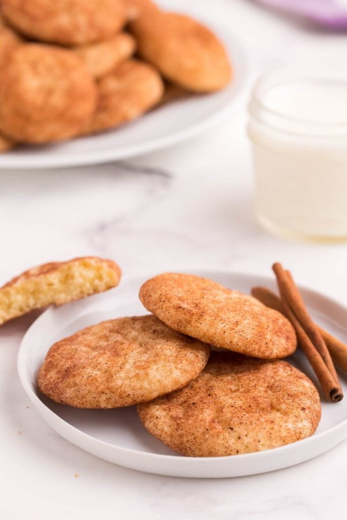 Snickerdoodle cookies on a white round plate with cinnamon sticks