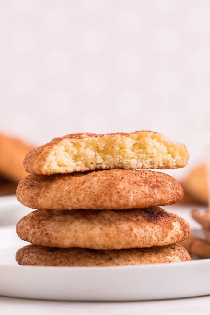 Snickerdoodles stacked on top of each other on a white plate with the top cookie broken in half