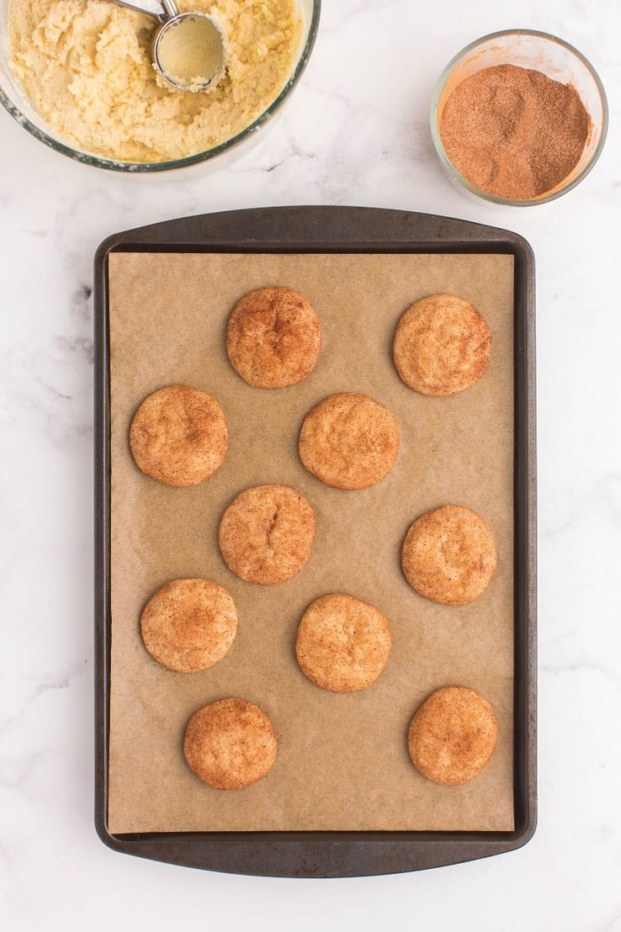 Baked snickerdoodle cookies without cream of tartar on a baking sheet lined with brown parchment paper