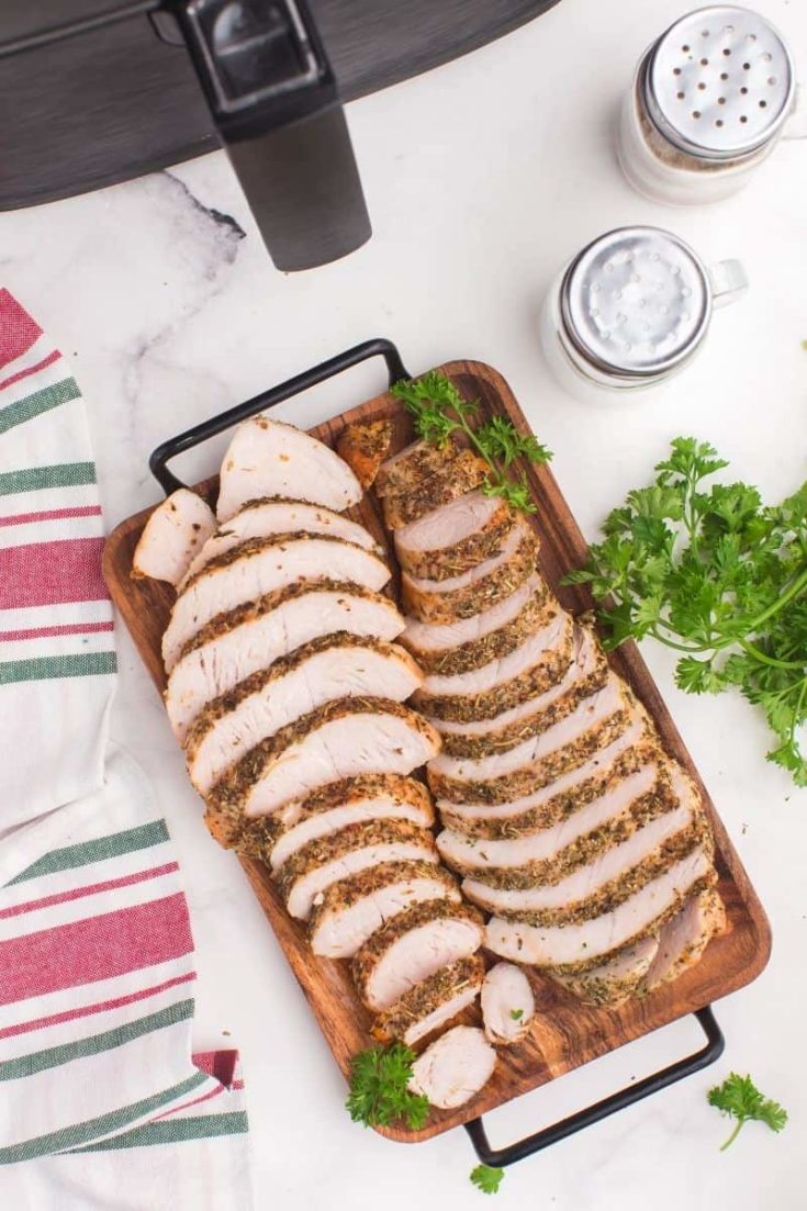 Air Fryer Turkey Tenderloins sliced up on a wooden serving platter in front of an air fryer