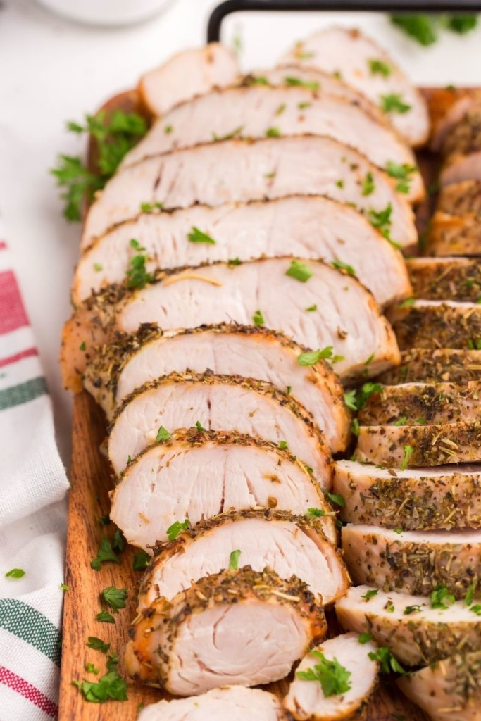 Closeup of sliced air fryer turkey breast tenderloins on a wooden serving tray