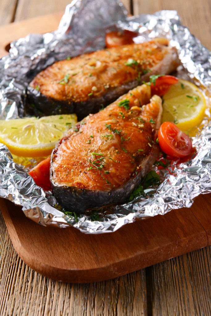 Fish wrapped in tin foil with fresh lemons and tomatoes