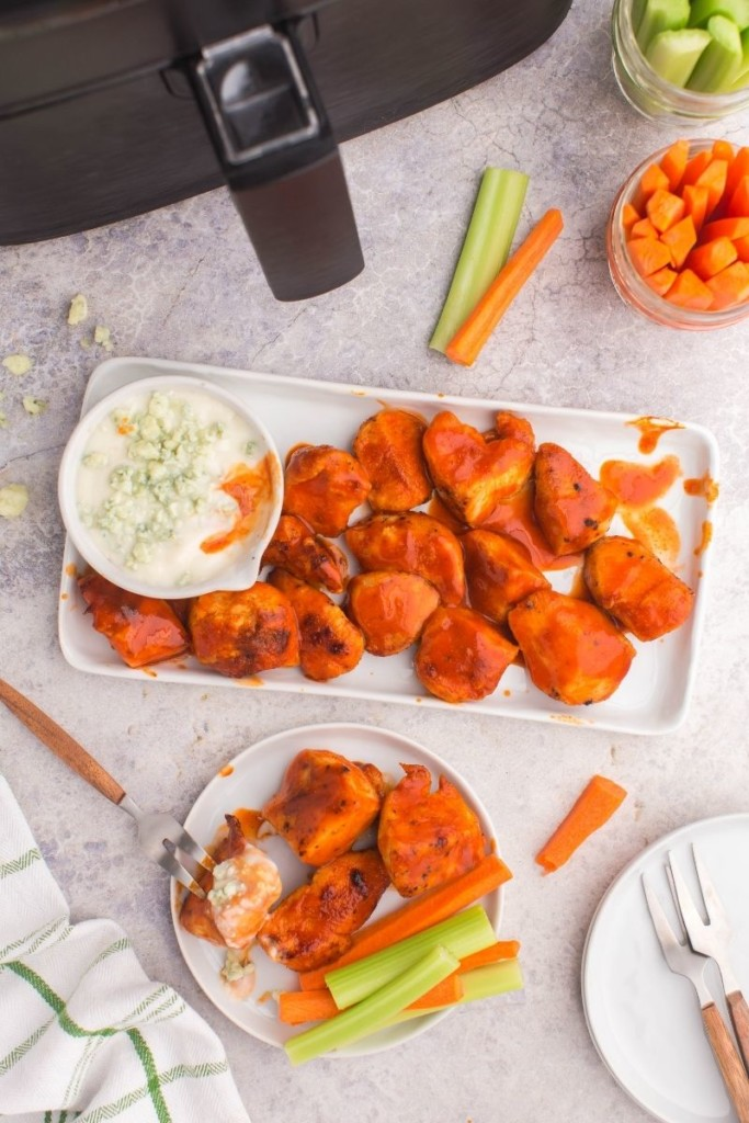 Air Fryer Boneless Wings on a rectangle serving platter covered with buffalo sauce and paired with blue cheese and carrots/celery