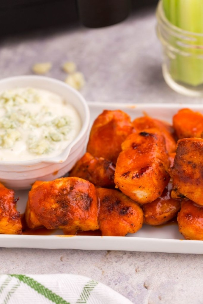 Closeup of boneless wings on a rectangular platter with blue cheese in a bowl