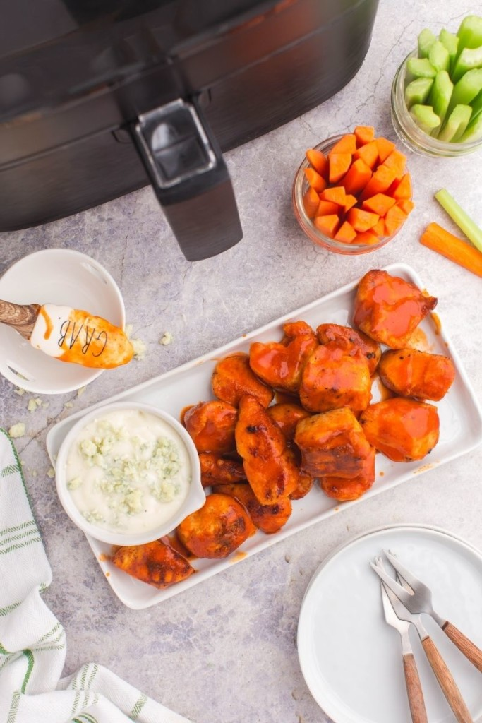 Boneless wings on a rectangle platter served with blue cheese, carrots, and celery in front of an air fryer