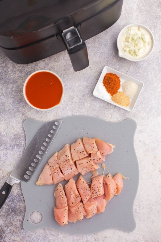 Chicken chopped up on a grey cutting board