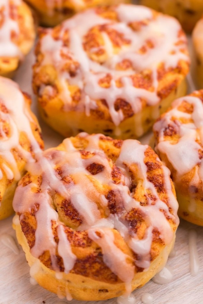Closeup of air fryer cinnamon rolls topped with icing