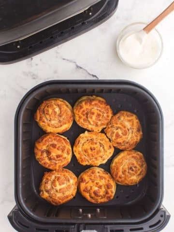 Cooked cinnamon rolls in air fryer basket