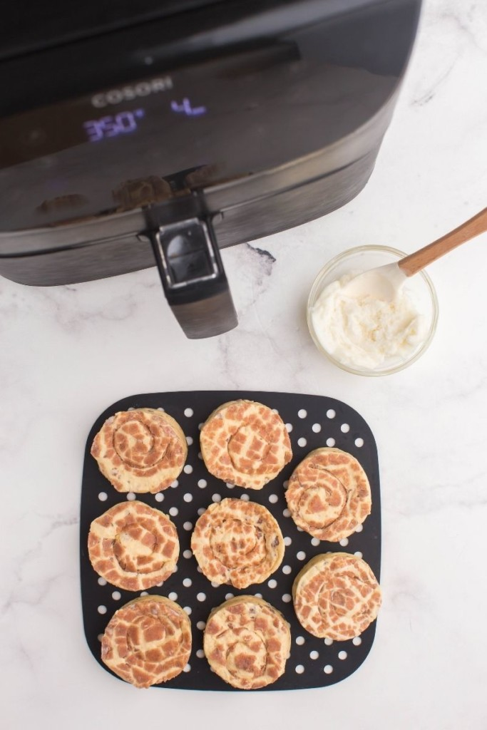 Cinnamon Rolls in front of an air fryer on a black silicone liner