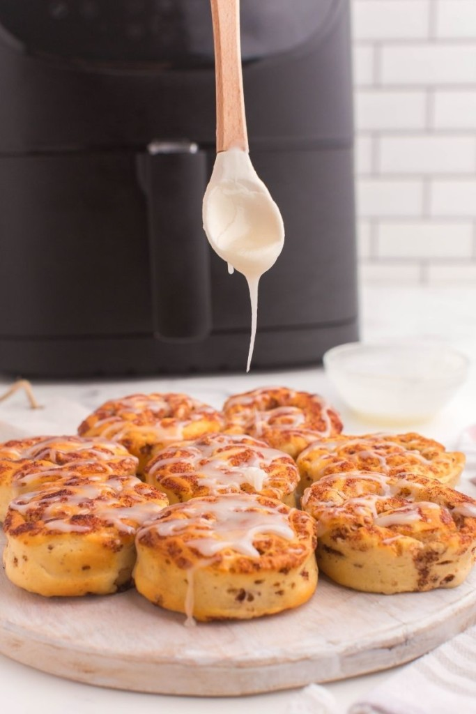 Icing being dripped onto cooked cinnamon rolls in front of an air fryer