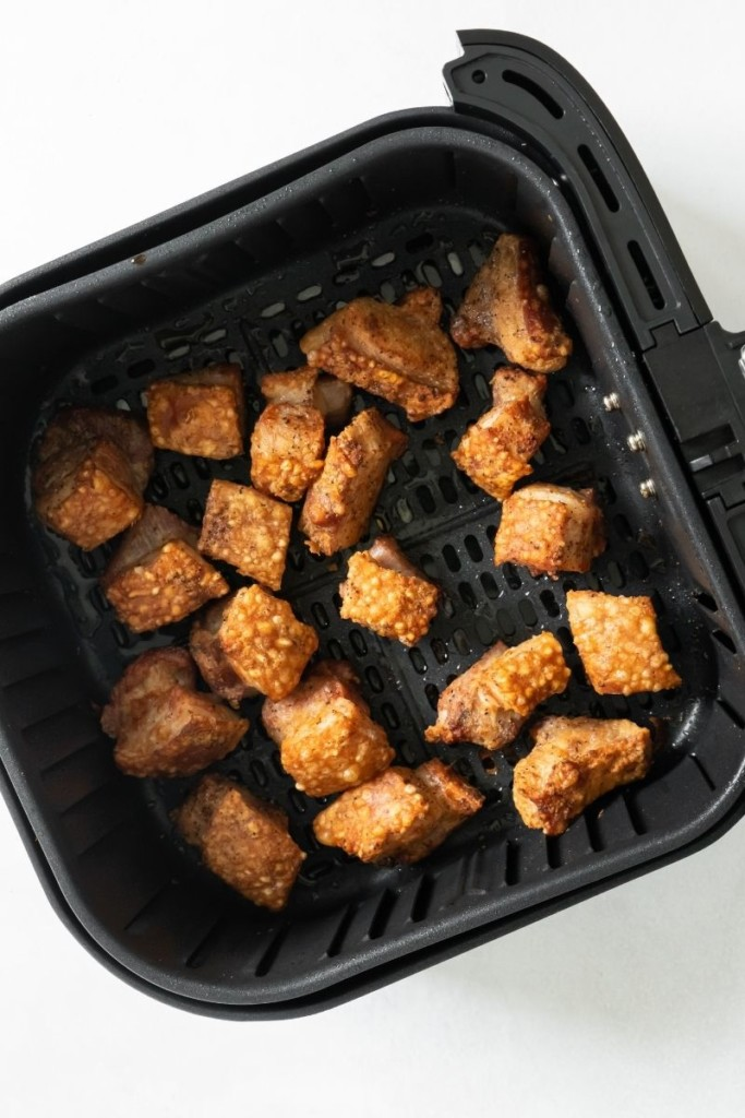 Cooked crispy pork belly in air fryer basket