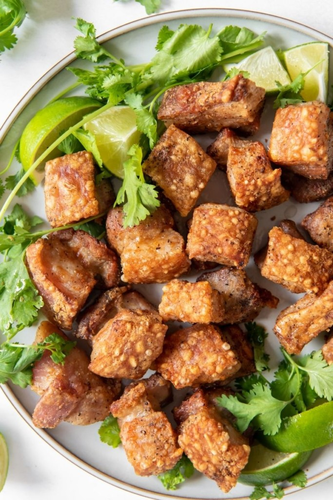 Crackling pork belly on a plate with green garnishes and lime wedges