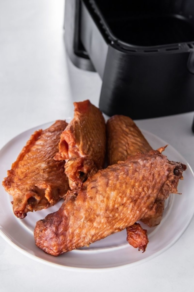 Raw pre smoked turkey wings in front of an air fryer