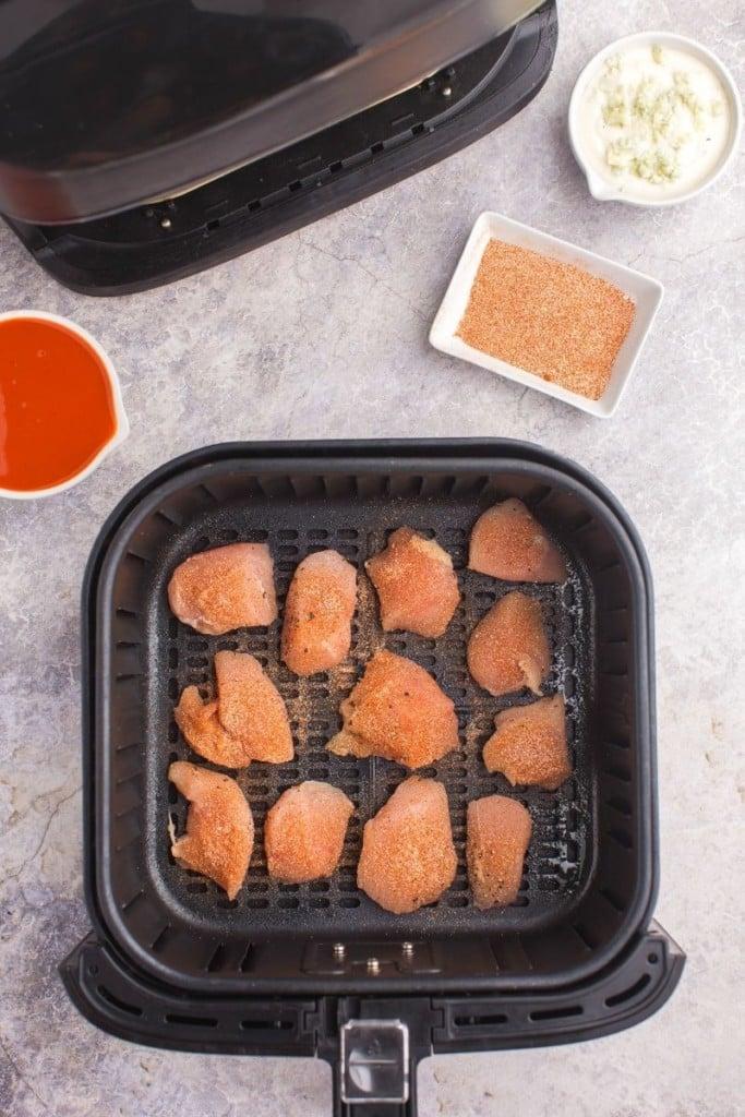 Seasoned boneless wings in air fryer basket