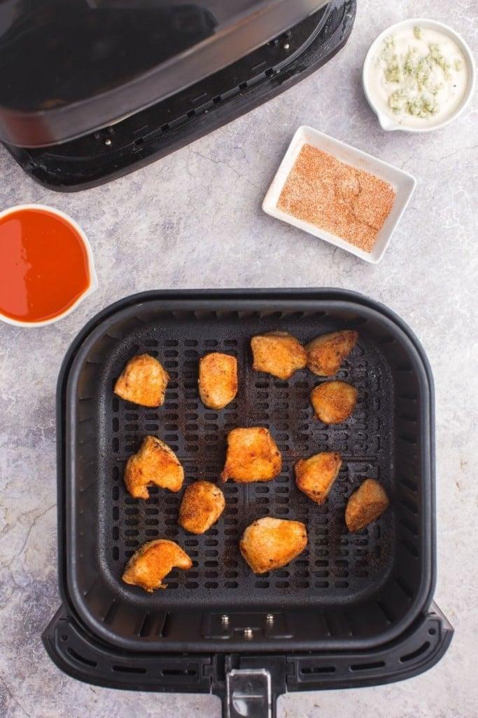 Cooked boneless wings in air fryer basket