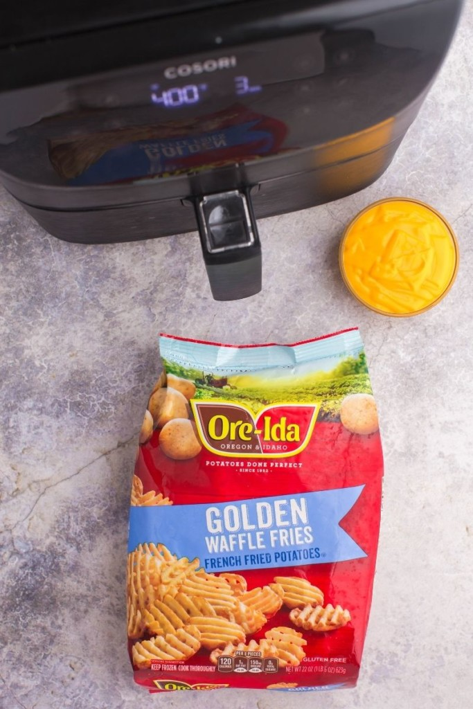 Ore Idea Golden Waffle Fries bag in front of an air fryer with a bowl of nacho cheese