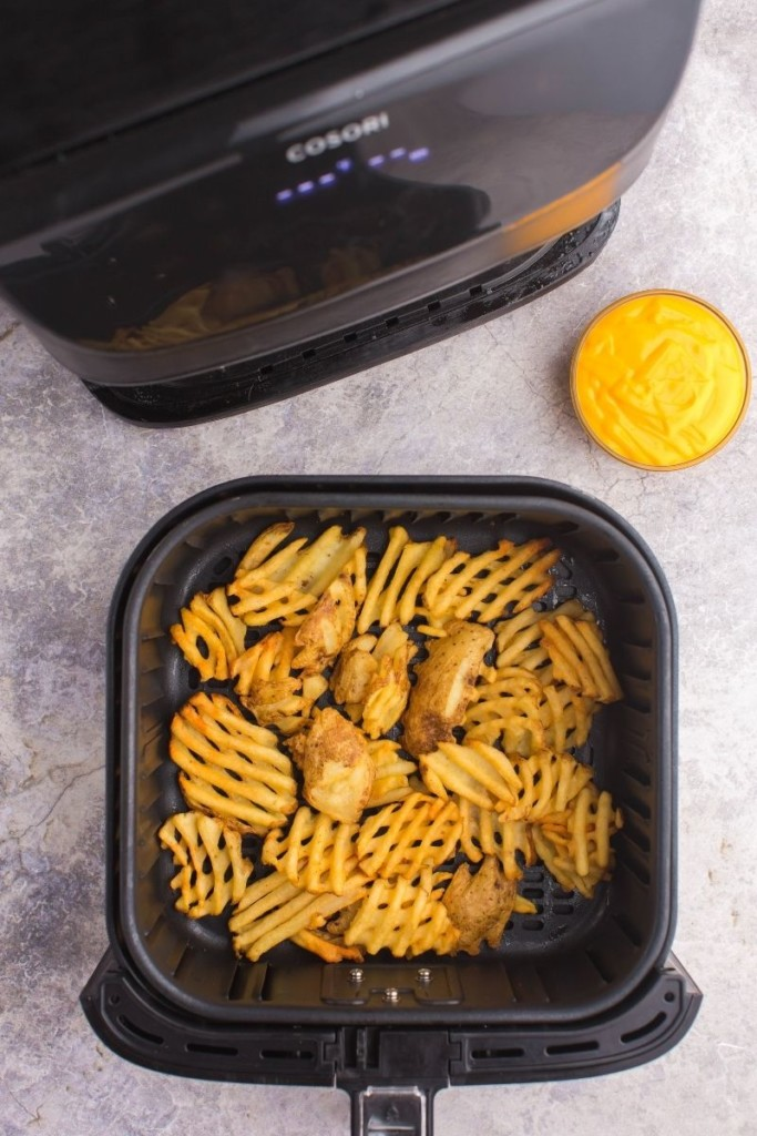 Frozen Waffle Fries in the air fryer cooked with a side of nacho cheese