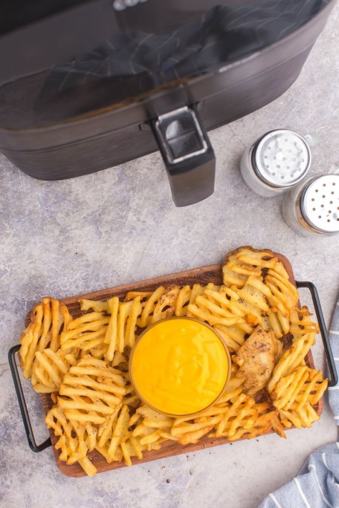 Overhead photo of cooked frozen waffle fries on a serving tray with nacho cheese in front of an air fryer