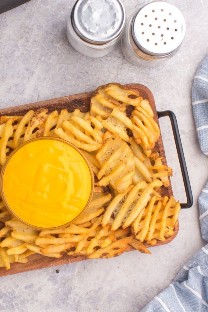Air Fryer waffle fries on a serving tray with nacho cheese in the middle