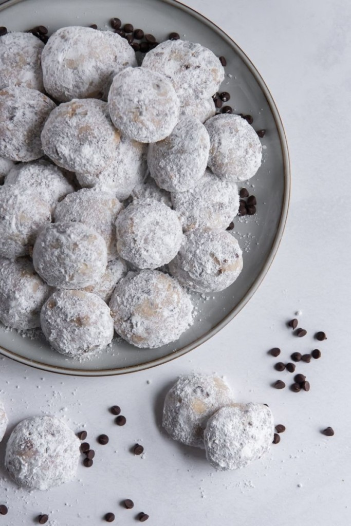 Snowball Cookies with no nuts on a grey round plate and some chocolate chips around it