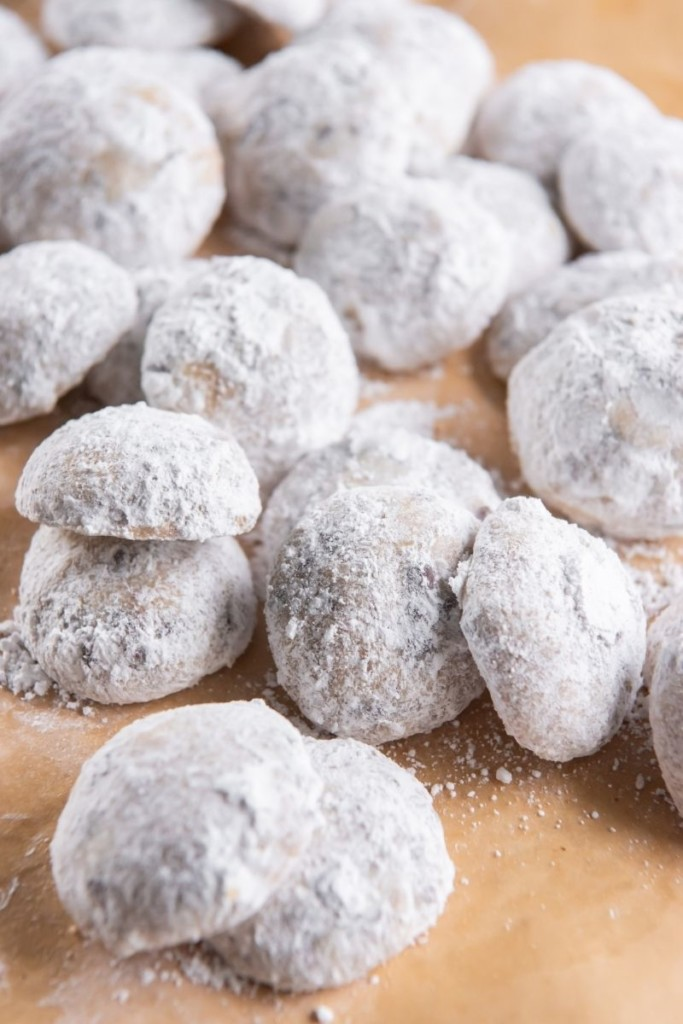 Snowball cookies with chocolate chips on brown parchment paper