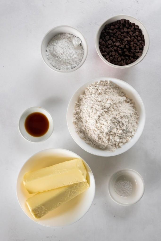Ingredients needed to make snowball cookies in separate bowls