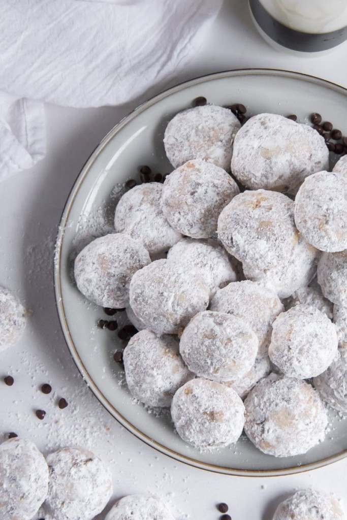 Snowball cookies on a round grey plate with snowball cookies and chocolate chips to the side of it
