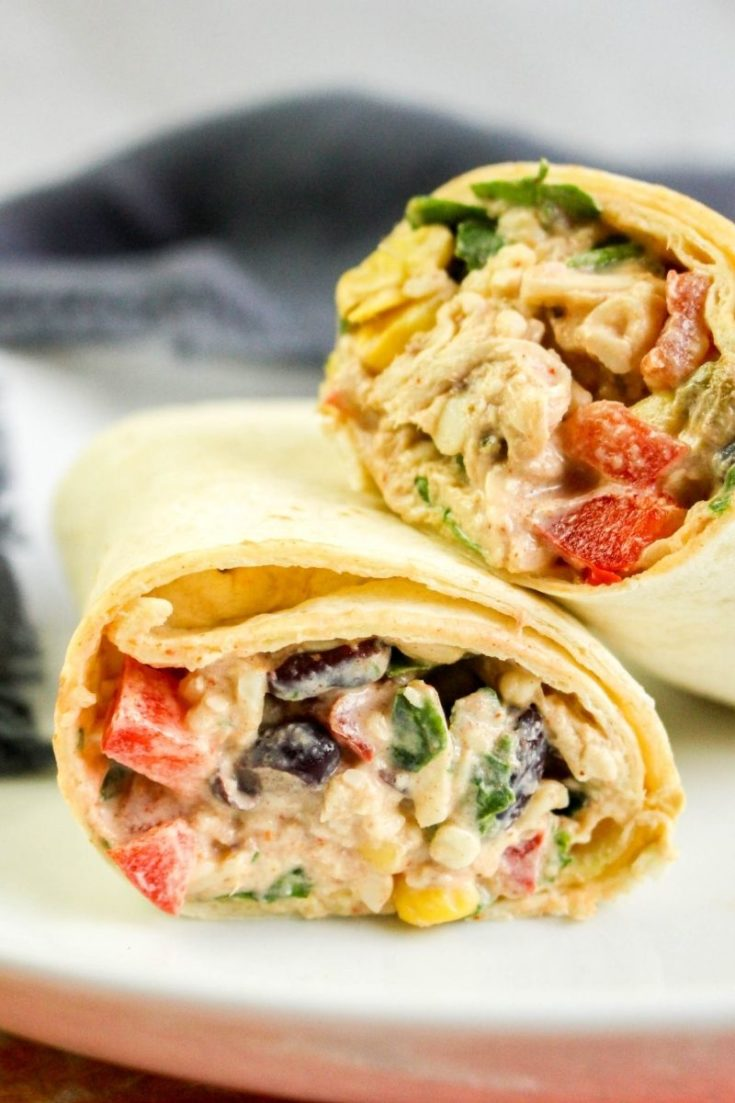 Southwest Chicken Wraps cut in half on a white plate and leaned on top of each other