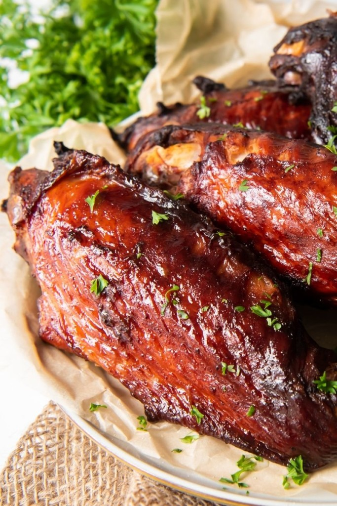 Turkey wings on a plate with parchment paper underneath of the wings