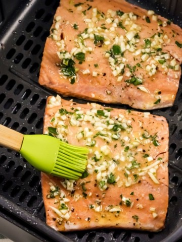 Air Fryer Salmon being basted by a silicone baster as an air fryer accessory