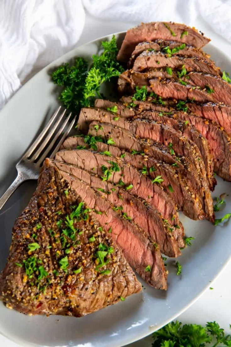Air Fryer London Broil sliced on a serving plate with a fork and parsley topping it