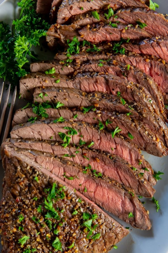 Closeup of sliced London Broil topped with parsley