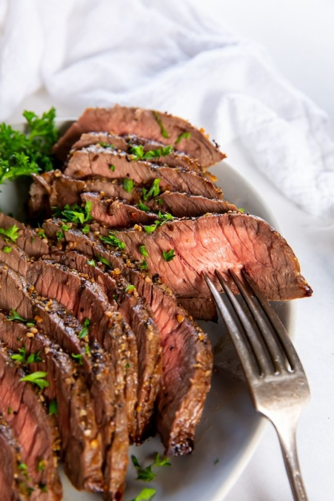 London Broil on a plate sliced with a fork inside a slice
