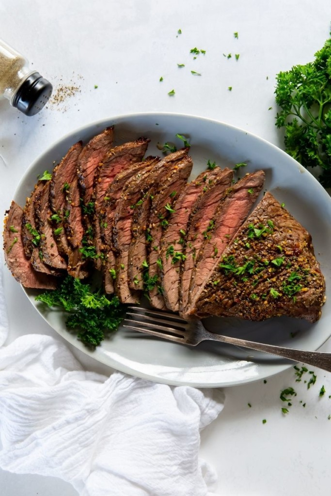 London broil on a white serving plate sliced with a fork and parsley on top