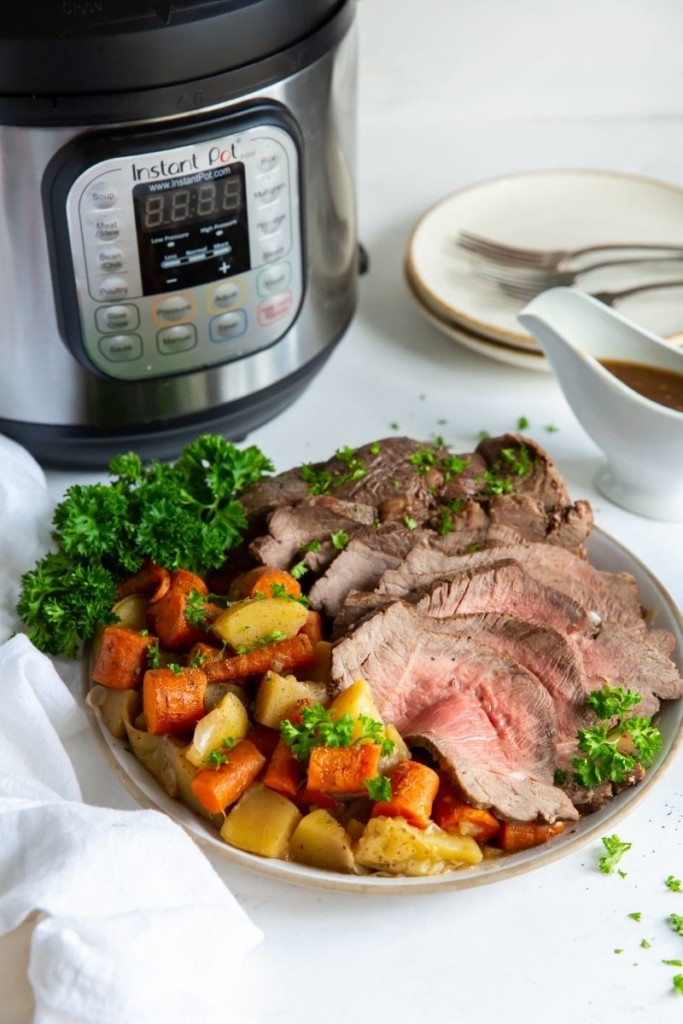 Sirloin tip roast with vegetables on a plate in front of an Instant Pot