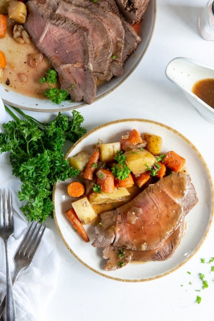 Plated instant pot roast on a plate with carrots and potatoes with serving plate in background