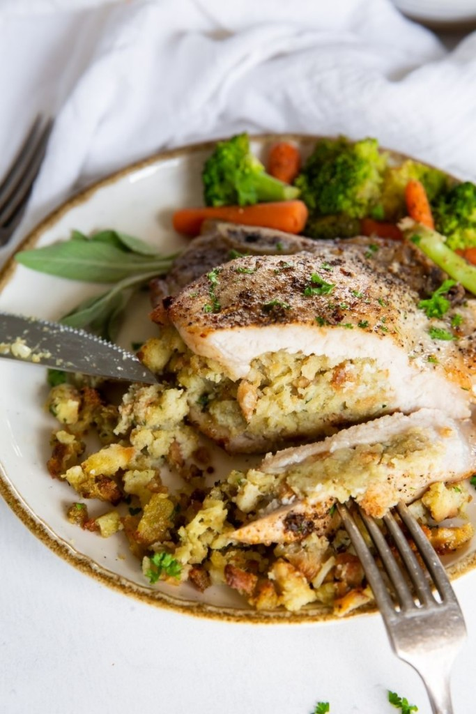 Sttuffed pork chop cut in half with stuffing showing on a white plate served with veggies (broccoli and carrots)