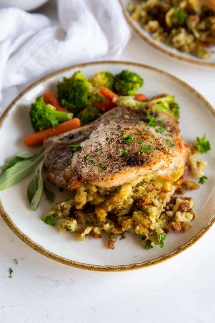 Air Fryer Stuffed Pork Chops on a plate with veggies on the side.